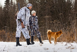 the hunter with his son and their dog on winter hunting