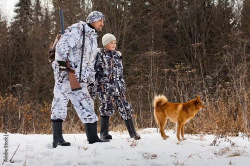 the hunter with his son and their dog on winter hunting - 75161172