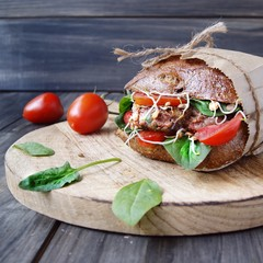 hamburger with black bread and tomatoes on table