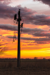 Single pylon with broken power lines hanging on it in dusk