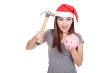 Asian girl with red santa hat hold hammer and  pink piggy bank