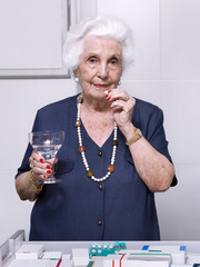 Portrait of an elderly woman in the kitchen, taking a medicine