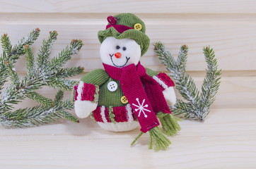 Cute snowman wearing a hat on a wooden surface