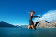 Beautiful Jumping Girl enjoying nature with her opened arms over