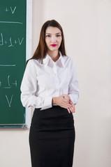 Beautiful young woman smiling near blackboard