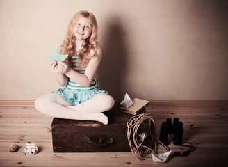 happy girl playing with toy sailing boat indoors