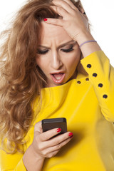 shocked young woman looking at her smartphone