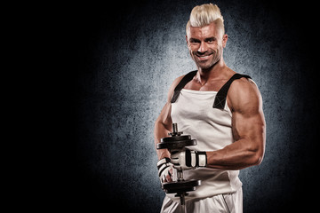 Athletic muscular young man with dumbbells on bright background