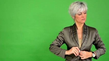 business middle aged woman adjusts clothing - green screen