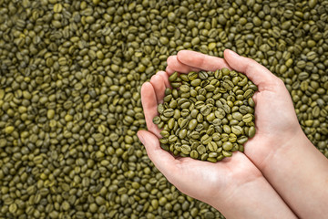 Green coffee beans in woman's hands.