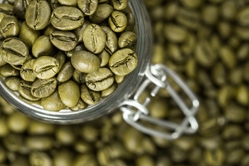 Green Coffee beans in a glass jar.