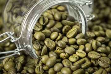 Green coffee beans in a glass jar.