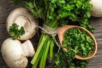 Fresh organic veggies. Mushrooms and parsley on wooden surface.
