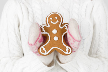 Young woman holding gingerbread man cookie. Woman in winter clot