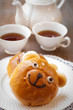 Sweet bun and cup of tea on wooden table