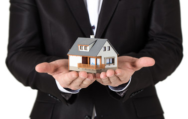 House in man's hands . Business man in suite holding a model hou