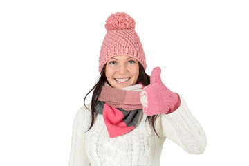 Attractive young woman in winter outfit showing thumbs up.