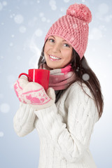 Smiley young woman in winter outfit with red cup.With snowflakes