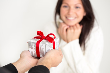 Man giving a Christmas gift to a beautiful young woman .
