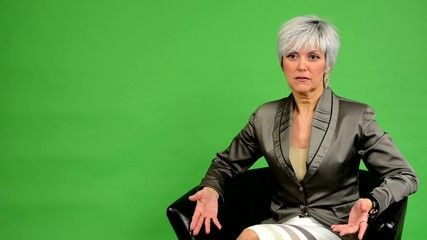 business middle aged woman sits and talks - green screen