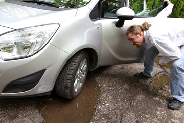 damaged car of road full of cracked potholes in pavement