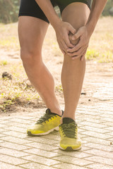 man runner hold her sports injured knee