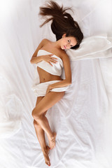 beautiful seminude woman with long hair on the bed