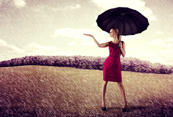 Pretty young business woman standing with umbrella in the rain