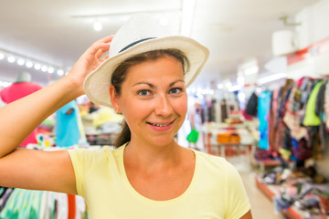 woman with a beautiful smile at the store chooses hat