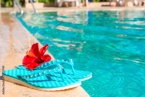 turquoise flip flops and flower on the edge of the pool - 75173749
