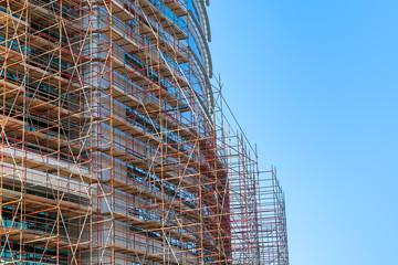 Modern building is under construction, metal scaffolding
