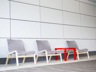chairs and small table on floor beside the modern wall
