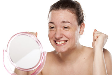 happy young woman looking at herself in the mirror