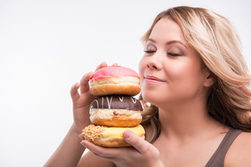 Young attractive woman with doughnuts isolated on white backgrou