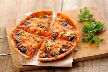 Pizza with olives and salmon and fresh greens