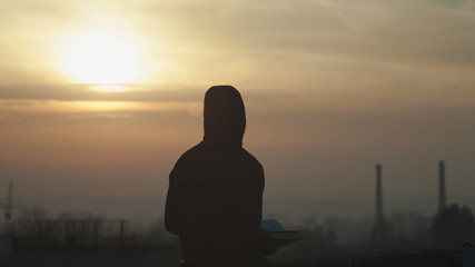 Silhouette of a young boy, reading a book on the roof of the