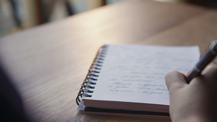 Close up of a woman writer hand writing in a notebook at home in