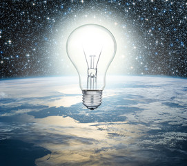 Light bulb over Earth on a background of the universe