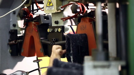 View of worker fixes boots in machine