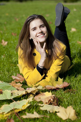 Happy young woman in yellow coat in autumn park