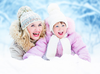 Happy parent mother and kid lying in snow outdoor