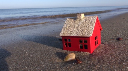 small house model on ocean beach and waves