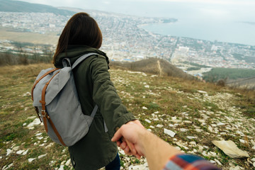 Tourist woman holding man's hand and leading him on nature
