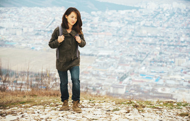 Traveler smiling woman trekking in highlands over the city