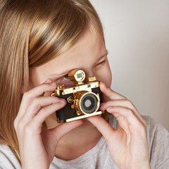 Girl photographer with gold retro camera