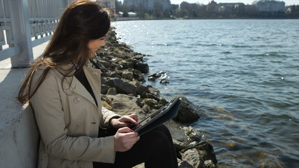 Woman on the beach, reading tablet computer and shows like