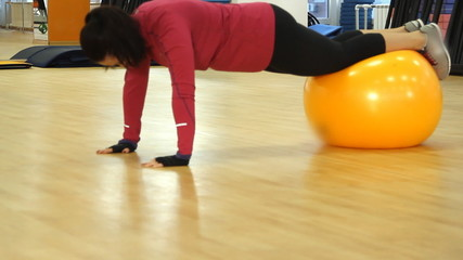 Young woman doing fitness exercise with fit ball