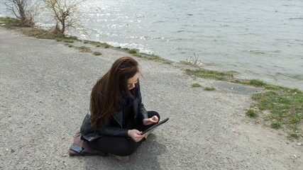 Smiling woman on the beach using her tablet shows like