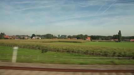 View of passing landscape from a train window. Belgium, Europe