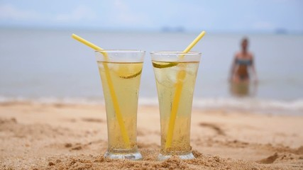 Two Tropical Fresh Juices on Beach with Girl in Bikini.